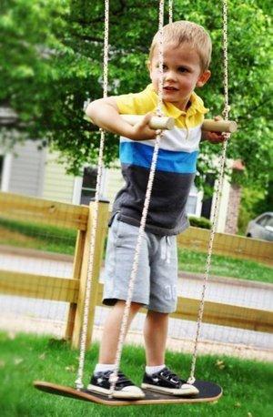 Мальчик из спортивной семьи  на качелях